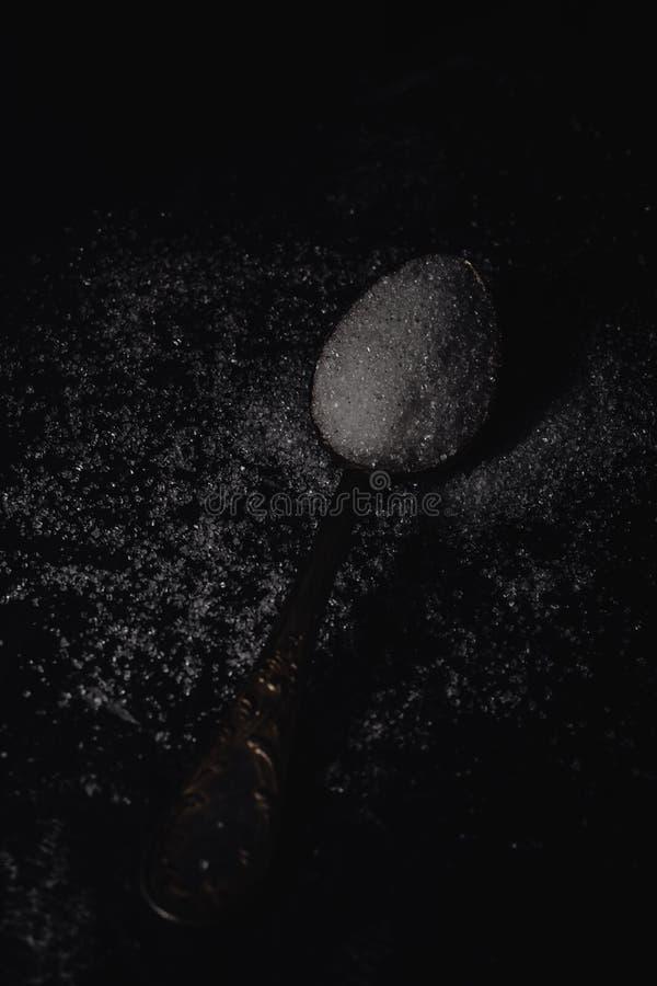 Темное фото ложки с белым сахаром на черной каменной предпосылке с космосом экземпляра, горизонтальным взглядом, низким основным  стоковые фото