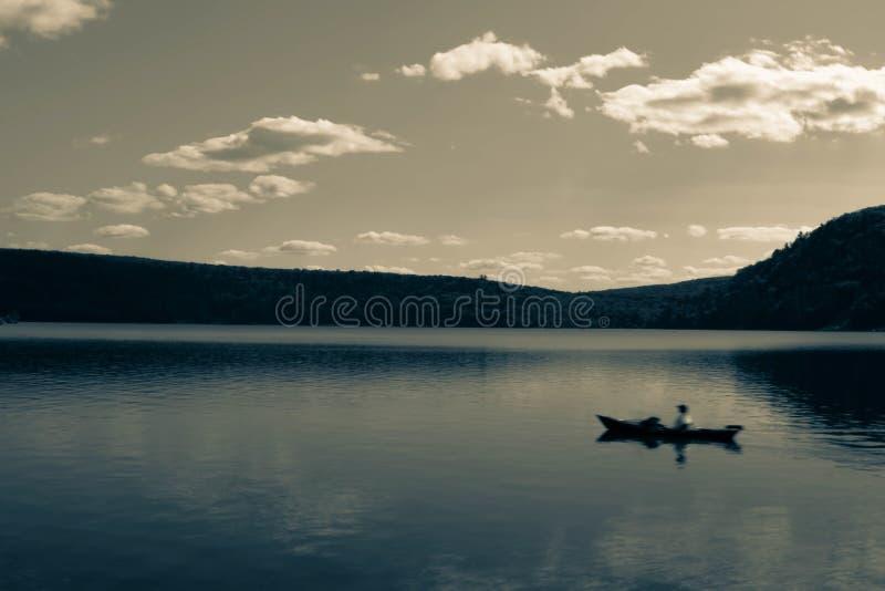 Темное художественное изображение WI озера дьявол, со шлюпкой плавая на воду, долгая выдержка стоковое фото