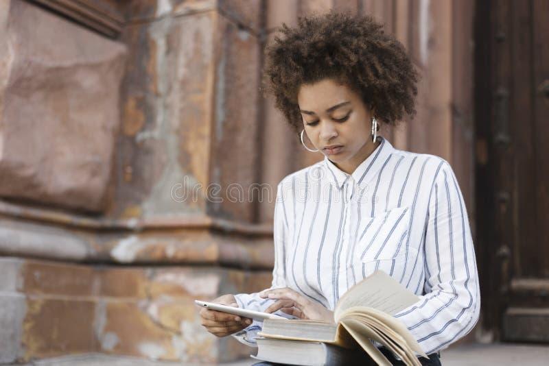 Темнокожая девушка сидя на шагах в улицу Она держит планшет и перезаписывает текст от книги На его ногах положите стоковые фотографии rf