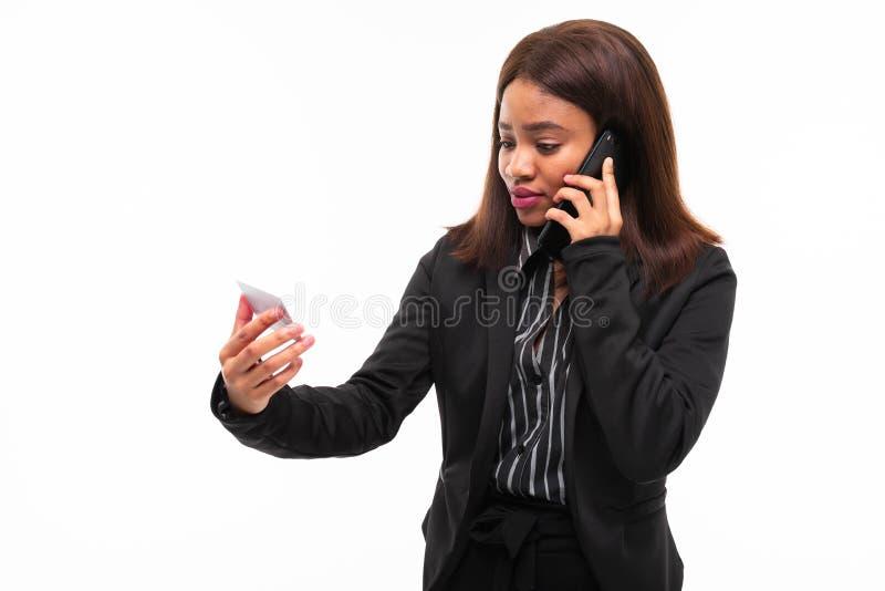 Темнокожая молодая smilling девушка вручая карту пока говорящ по телефону изолированному на белой предпосылке стоковая фотография rf