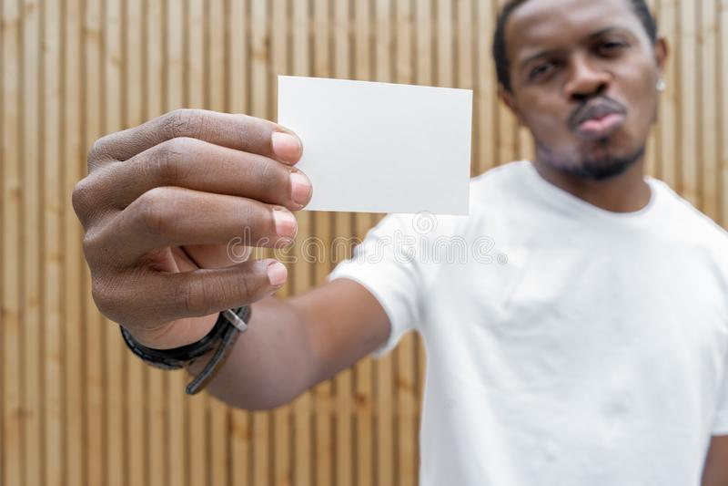 Темнокожий человек в белой футболке показывая пустую визитную карточку к камере стоковое фото