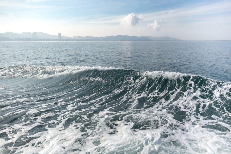 Темносиняя океанская волна с горой и небом стоковые изображения rf