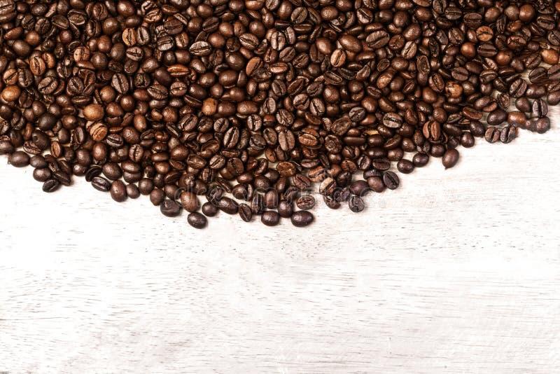 Темнота зажарила в духовке конец обоев эспрессо Брайна кофеина кофейных зерен вверх Зажаренный макрос текстуры кофейных зерен стоковое фото rf