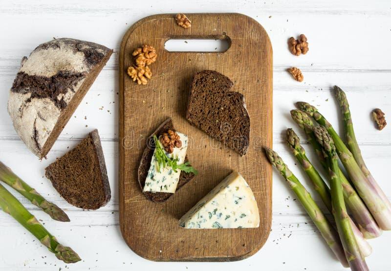 Темнота отрезала хлеб, голубой сыр с гайками на деревянной разделочной доске украшенной с спаржей Плоское положение, взгляд сверх стоковая фотография