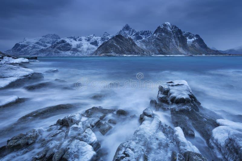 Темные облака над фьордом в Норвегии в зиме стоковая фотография rf