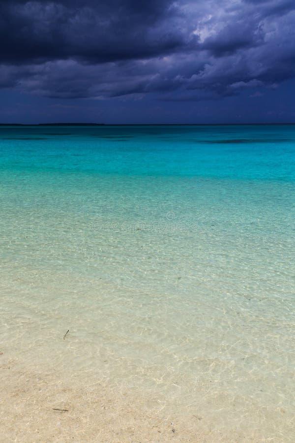 Темные облака шторма над дезертированным пляжем стоковое фото