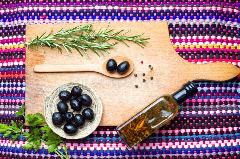 Темные оливки с специями на деревянной доске стоковое изображение rf