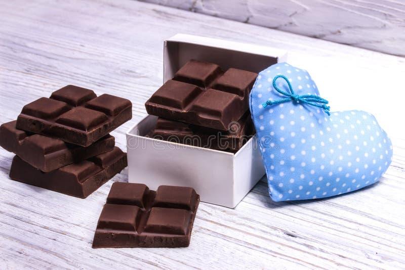 Темные шоколадные батончики и голубое сердце стоковые изображения rf