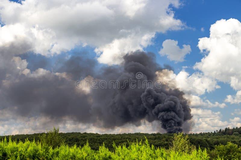 Темный дым огня после аварии тележки шоссе против красивого неба в августе стоковые изображения rf