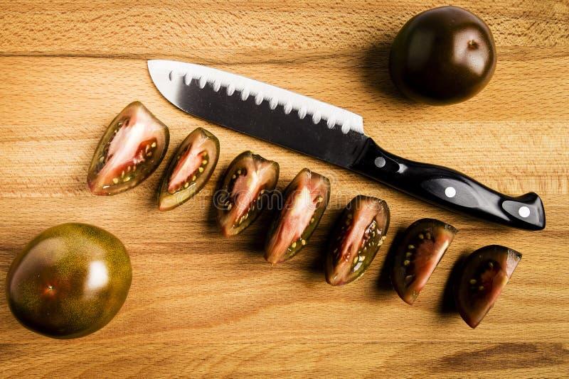 Темный - красные все томаты и отрезок kumato с ножом стоковое фото