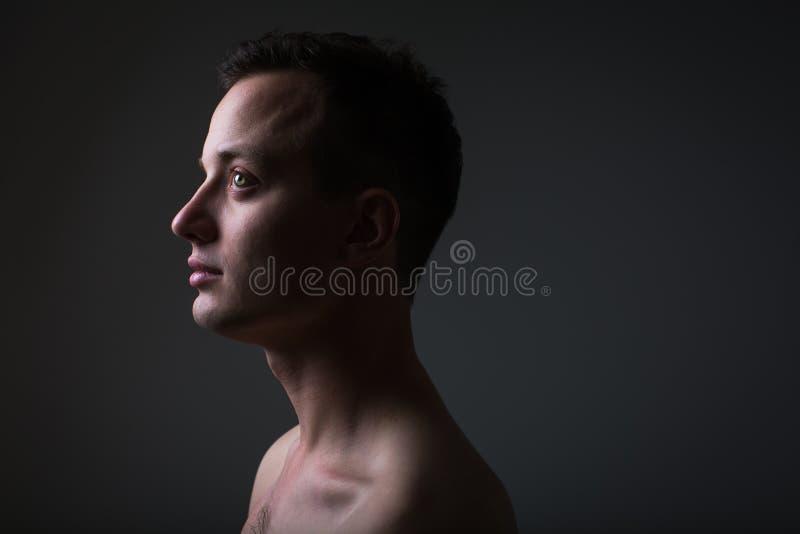 Темный низкоключевой портрет молодого человека на сером фоне стоковые изображения rf