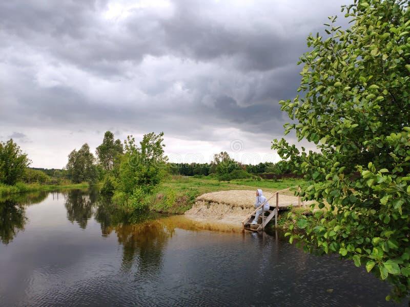 Темный пасмурный взгляд реки шторма Женщина на пристани стоковое изображение