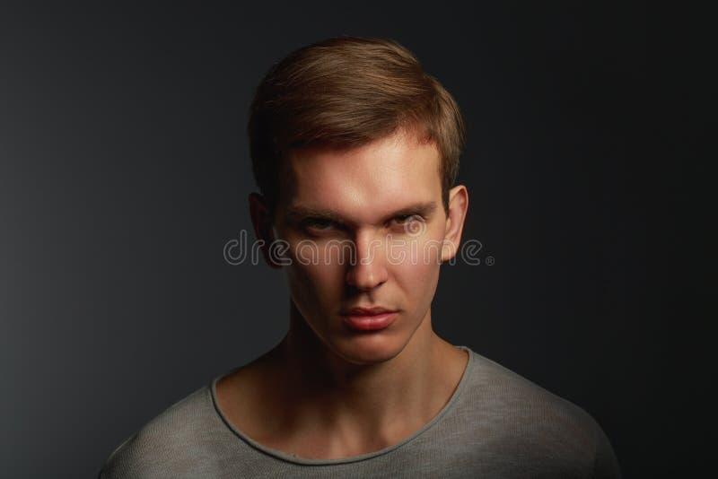 Темный портрет моды молодого сердитого человека с тенями контраста стоковое фото rf