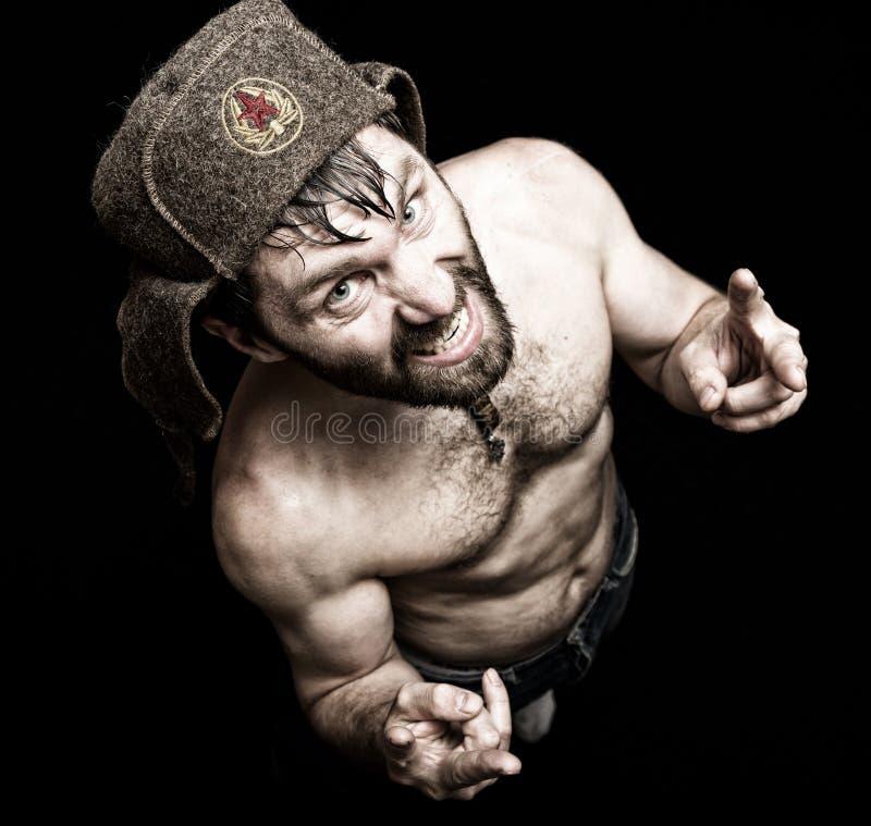 Темный портрет страшного злого зловещего бородатого человека с ухмылкой, делает знаки различной руки стоковое фото rf