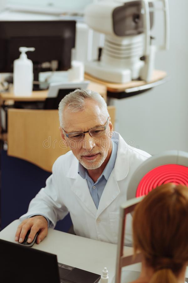 Темн-наблюданное чувство глазного врача занятое рассматривающ видимость глаза женщины стоковое изображение