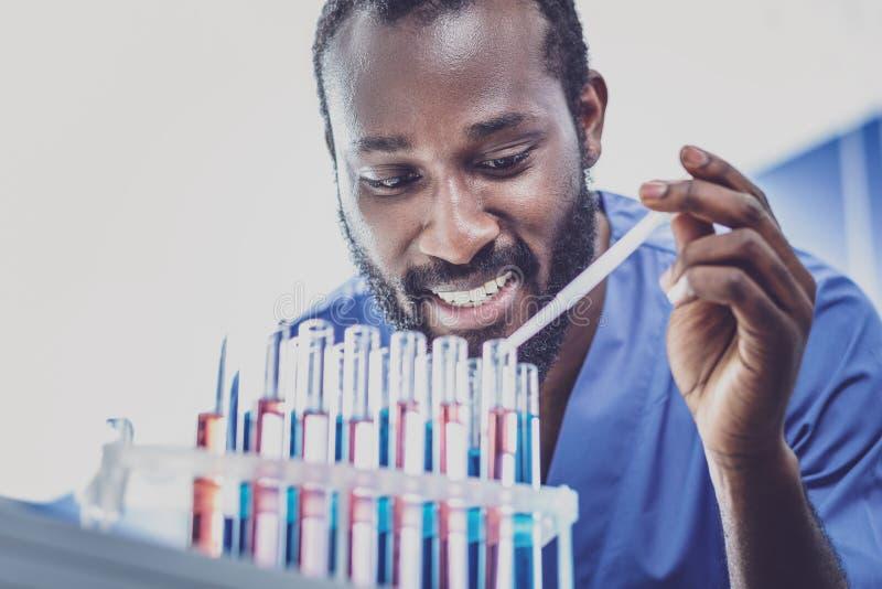 Темн-наблюданный молодой биолог работая на исследовании стоковое изображение rf