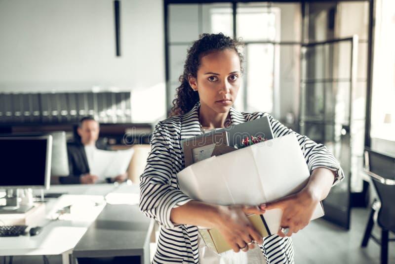 Темн-наблюданный стажер принимая ее коробку со штатом после покидать офис стоковая фотография