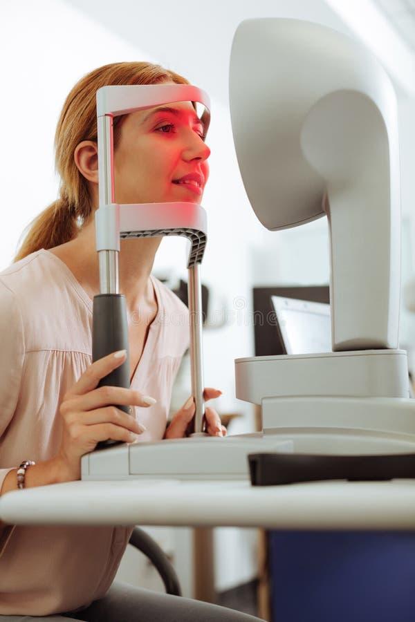 Темн-с волосами женщина усмехаясь пока навещающ офтальмолог стоковая фотография rf