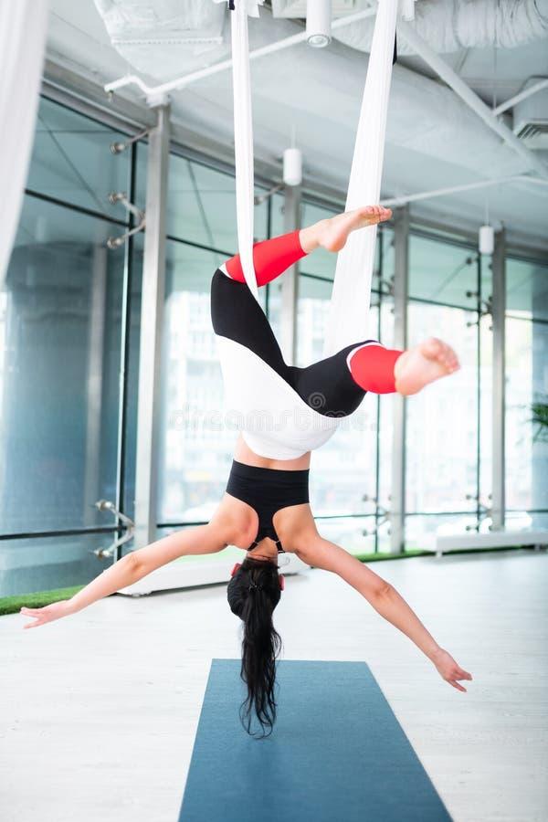 Темн-с волосами женщина с ponytail чувствуя свободно делающ воздушную йогу стоковые фото