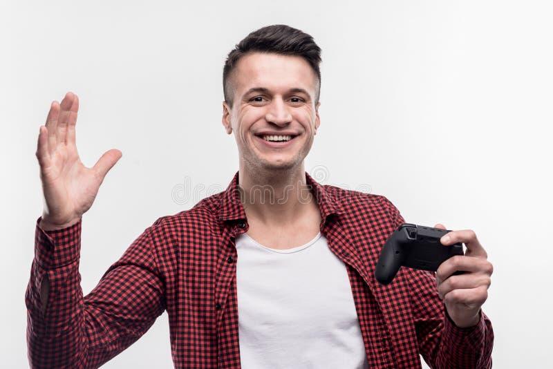 Темн-с волосами испуская лучи человек держа черный кнюппель играя видеоигру стоковые фотографии rf