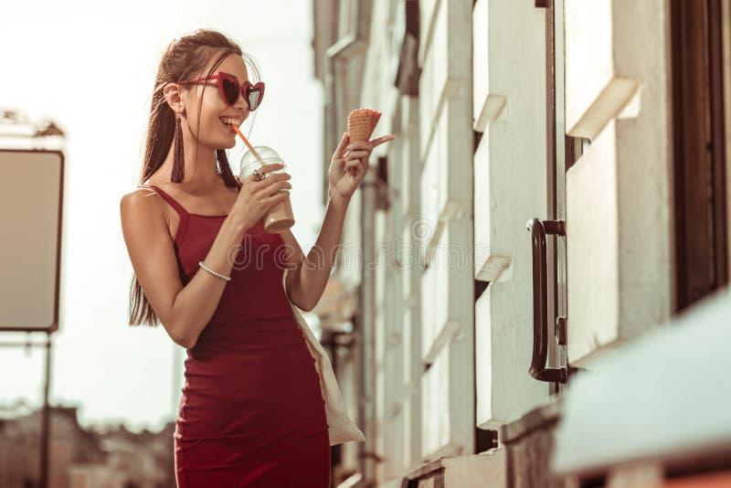 Темн-с волосами приятный заколдовывая лед-latte дамы выпивая пока идущ улицы стоковые фото