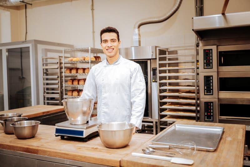 Темн-с волосами профессиональный хлебопек работая в современной просторной кухне стоковое изображение rf