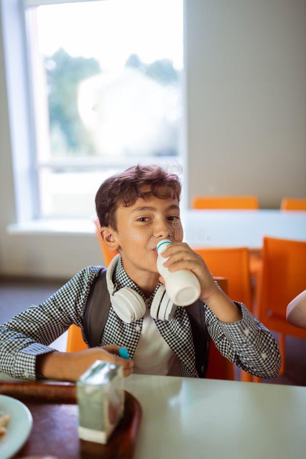 Темн-с волосами школьник с наушниками на питьевом молоке шеи стоковое фото