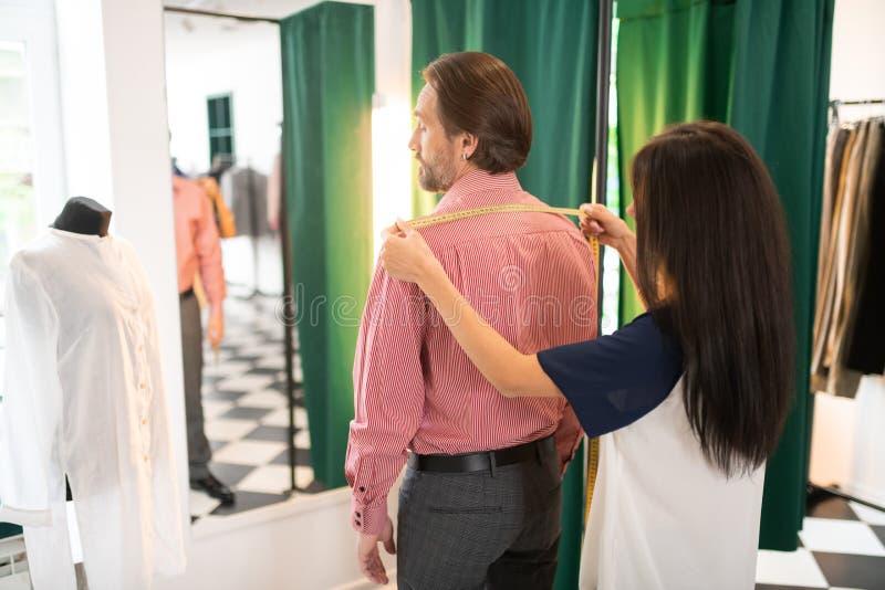 Темн-с волосами alluring консультант получая измерения привлекательного красивого симпатичного мужчины стоковая фотография