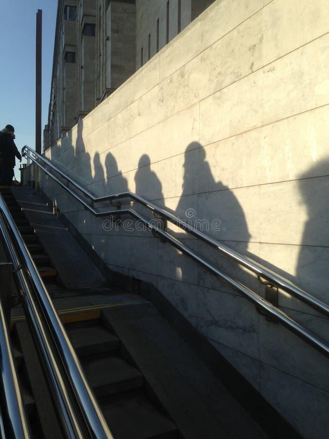 Тени людей идя из метро стоковые изображения