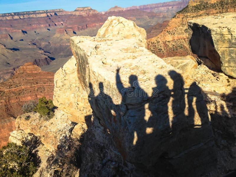 Тени туристов на валунах в гранд-каньоне в Соединенных Штатах стоковое изображение