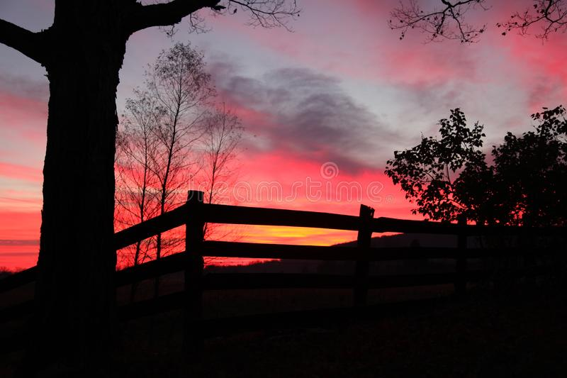 Тени цвета на заходе солнца над сельской загородкой стоковое изображение
