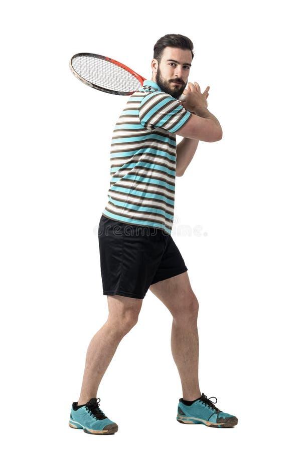 Теннисист ждать для того чтобы ударить шарик держа ракетку с обеими руками в представлении удара слева стоковые изображения rf