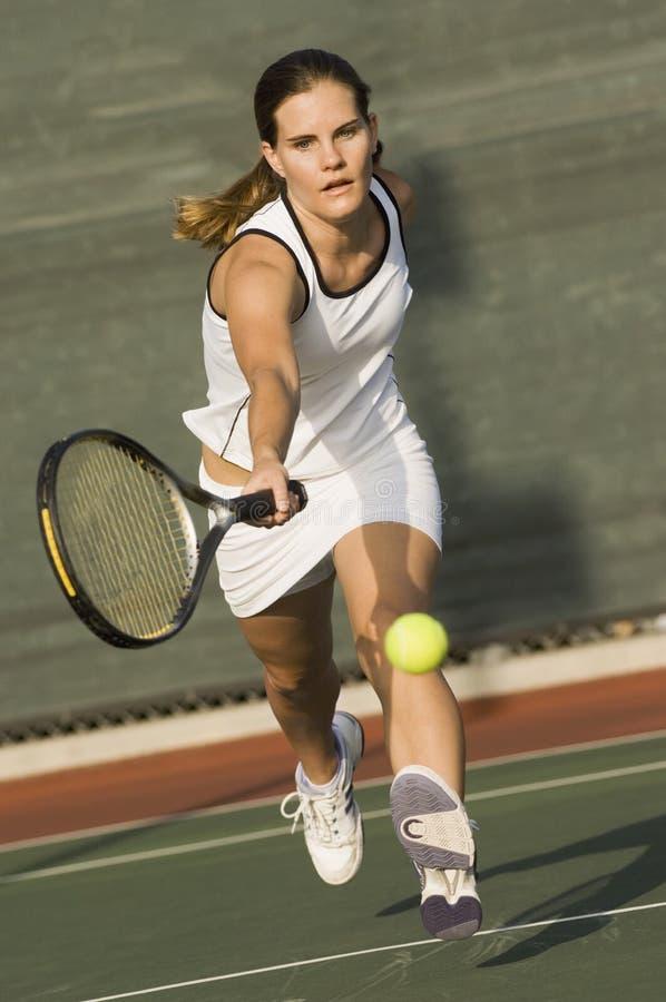 Теннисист достигая для того чтобы ударить шарик стоковая фотография