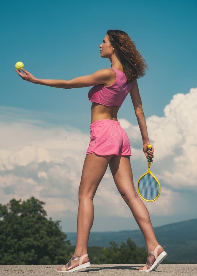 Теннис прямой ломать Сексуальная атлетическая женщина играя теннис на открытом воздухе Женщина пригонки держа теннисный мяч и рак стоковое изображение rf