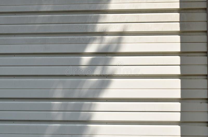 Тень дерева на белых текстуре и предпосылке двери жалюзи утюга стоковые изображения