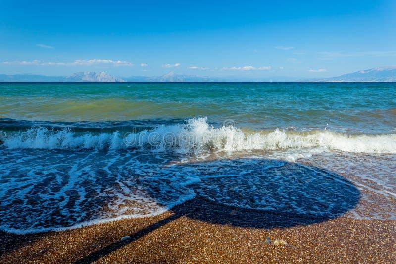 Тень парасоля в волнах на греческом Pebble Beach стоковые фото