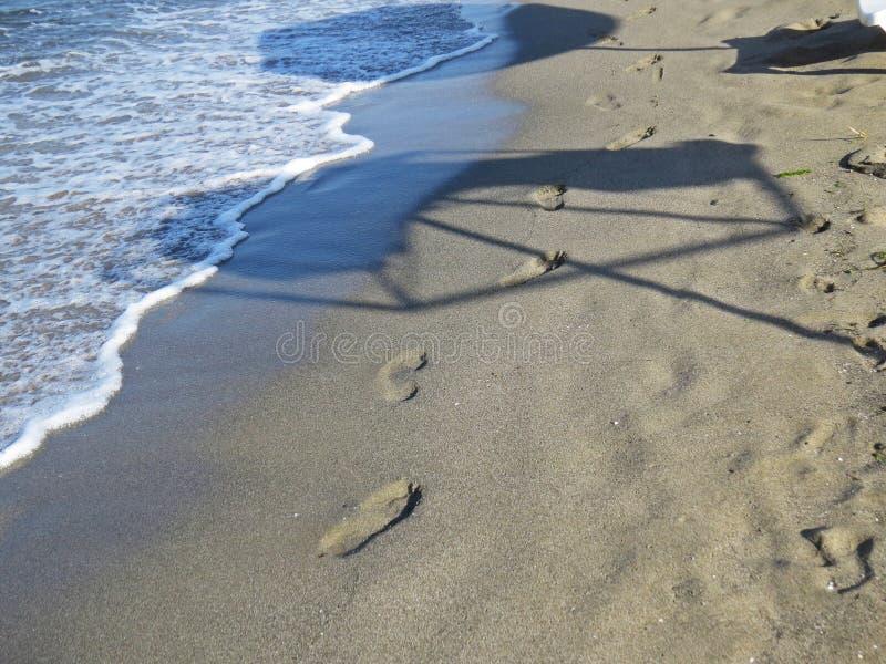 Тень разрушенного зонтика парасоля видимого на песчаном пляже во время экзотических каникул стоковое фото rf