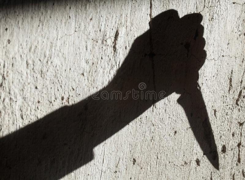Тень руки держа нож стоковое фото