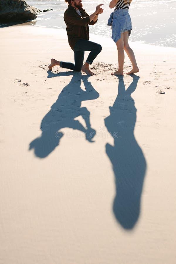 Тень человека предлагая женщину на пляже стоковая фотография rf