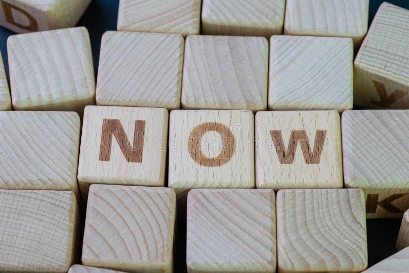 Теперь, этот момент времени, останавливает концепцию промедления, блок куба деревянный с алфавитом для того чтобы совместить слов стоковая фотография