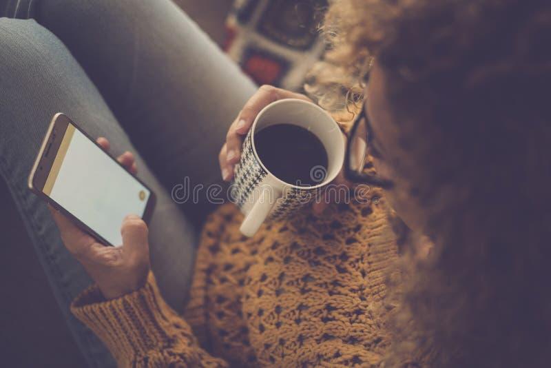 Теплая домашняя сладкая атмосфера шестка для дамы среднего возраста используя технологию интернета мобильного телефона с одной ру стоковые изображения