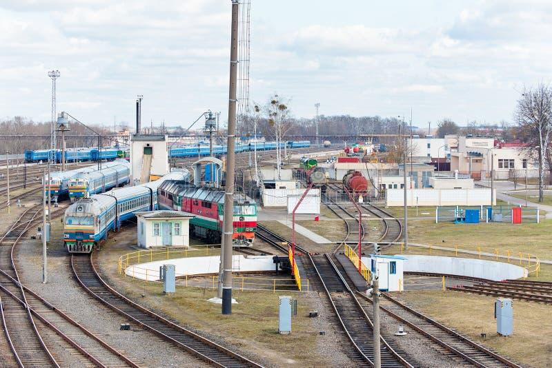 Тепловозы и экипажи стоят в депо около железнодорожного turntable стоковое фото rf
