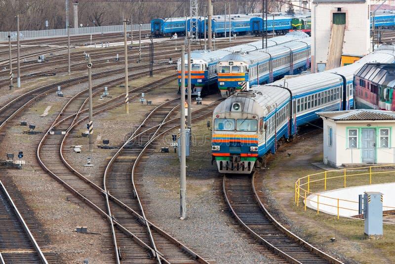 Тепловозы и экипажи стоят в депо с сериями вилок и рельсов рельса около железнодорожного turntable стоковое фото