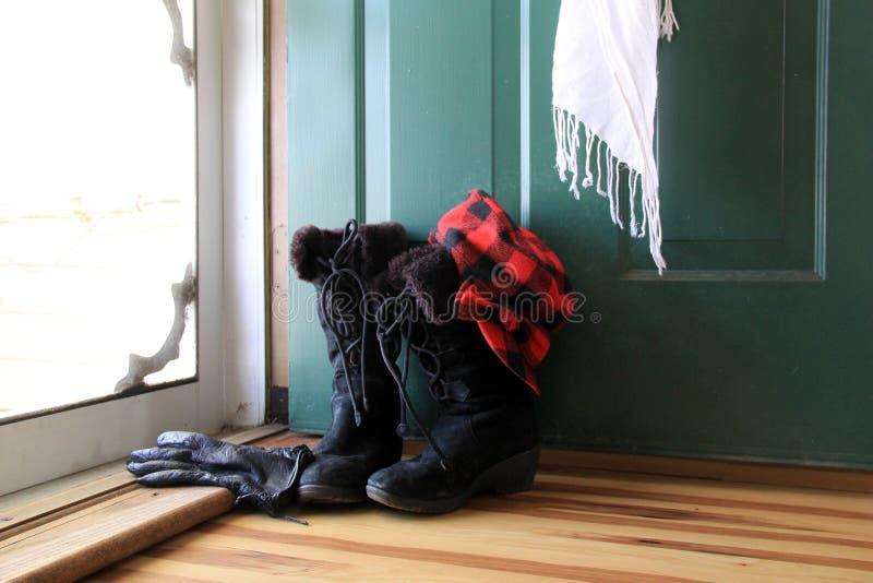 Теплое и приветствующее изображение ботинок, перчаток, шарфа и шляпы зимы дам около открыть двери дома стоковое изображение rf
