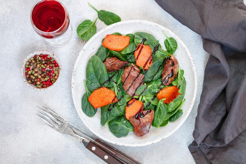 Теплые салат шпината с куриной печенью и испеченной тыквой со специями и бальзамический стоковые изображения rf