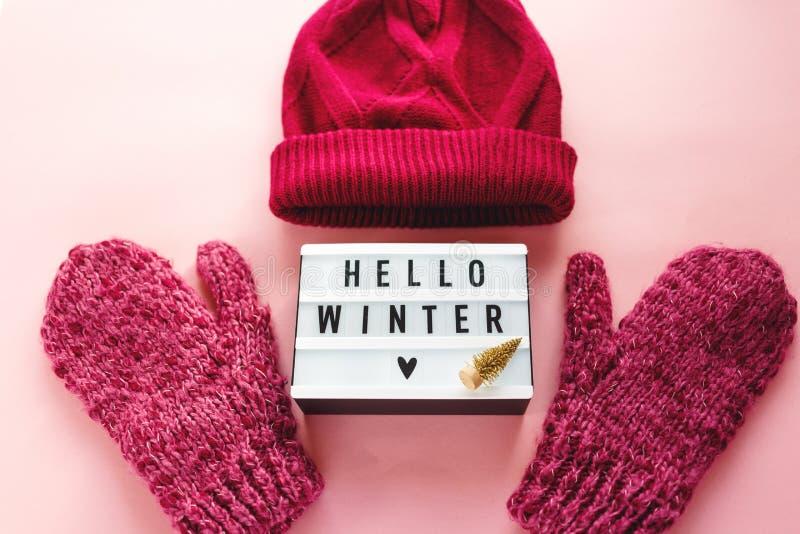 Теплые, уютные шляпа одежды зимы, mittens, lightbox и украшения рождества как рамка на пастельной розовой предпосылке стоковая фотография