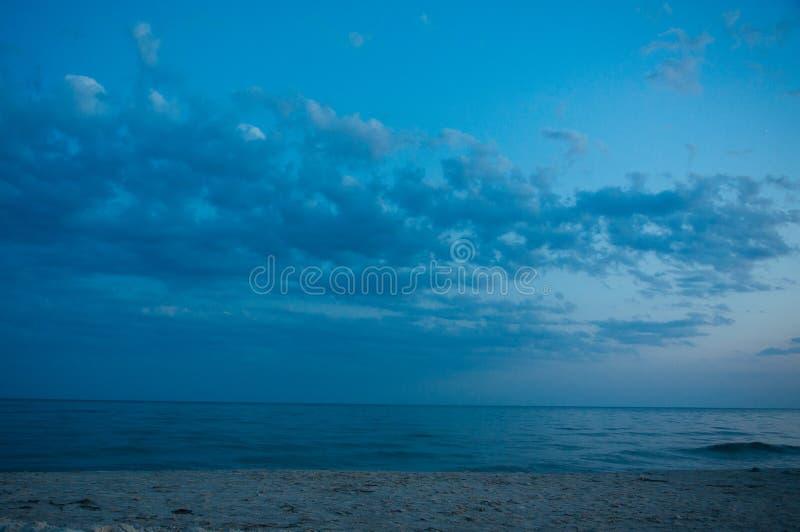 Теплый голубой заход солнца на береге океана, моря, на заходе солнца на лете стоковое фото