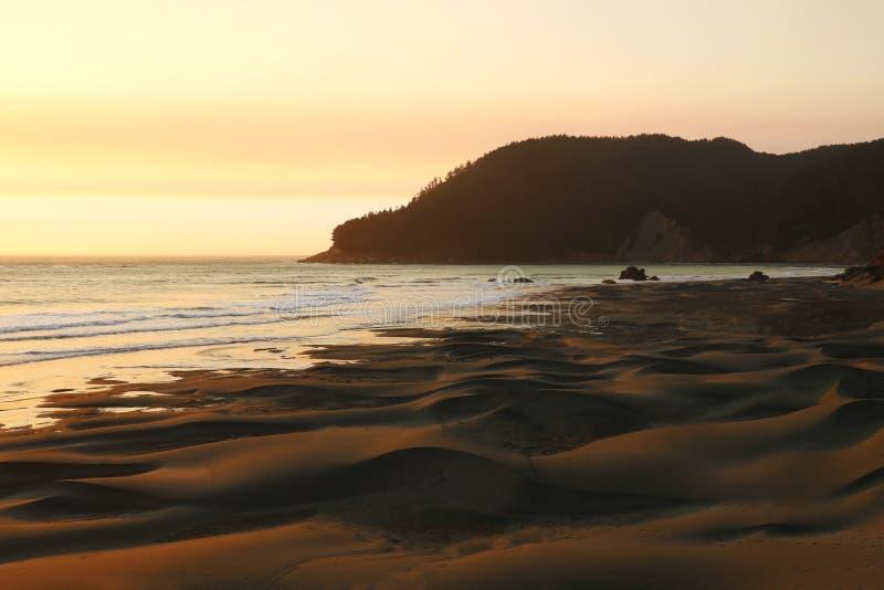 Теплый заход солнца над Тихим океаном и пляжем, популярным пятном для серферов стоковое фото rf