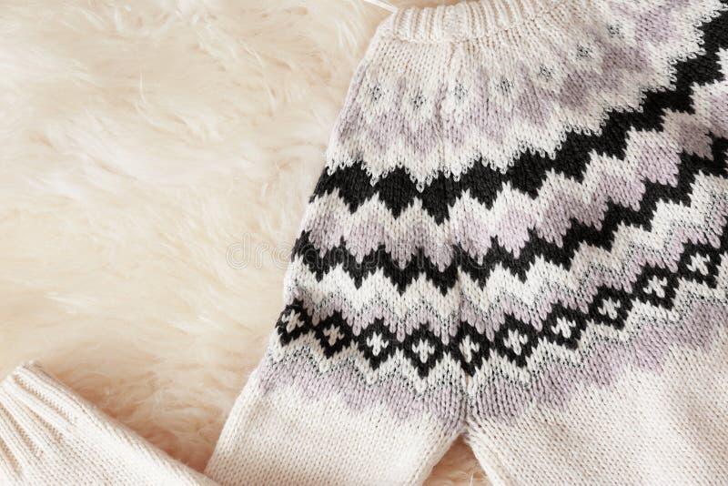 Теплый связанный свитер на расплывчатом ковре стоковое изображение