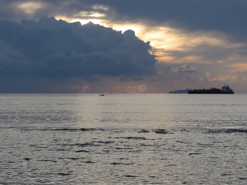Теплый заход солнца моря с грузовим кораблем и малой рыбацкой лодкой на горизонте Ливневые облака Giants в небе Тоскана, Ital стоковая фотография